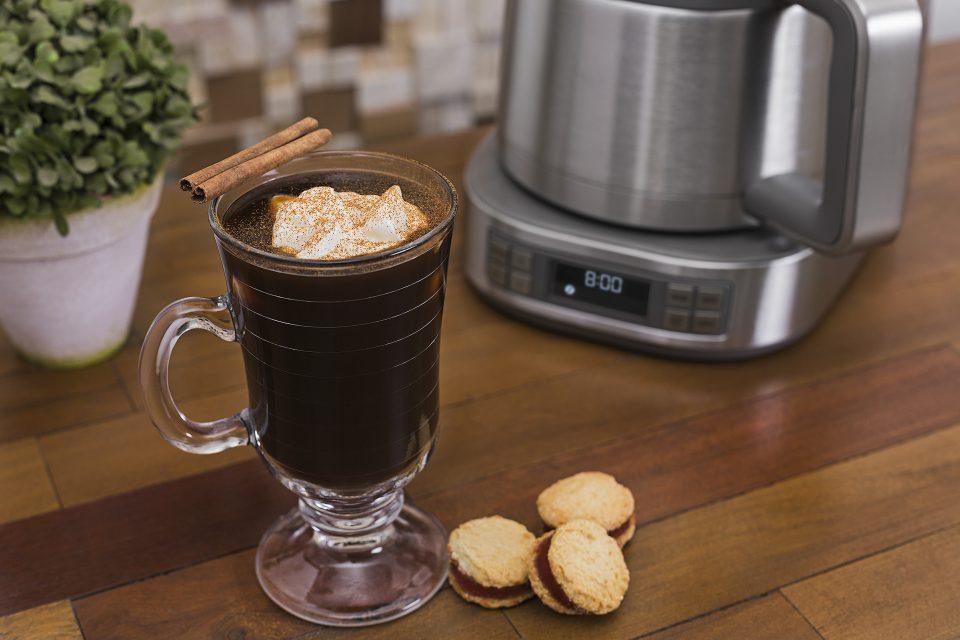 Imagem do café com especiarias e a cafeteira de fundo