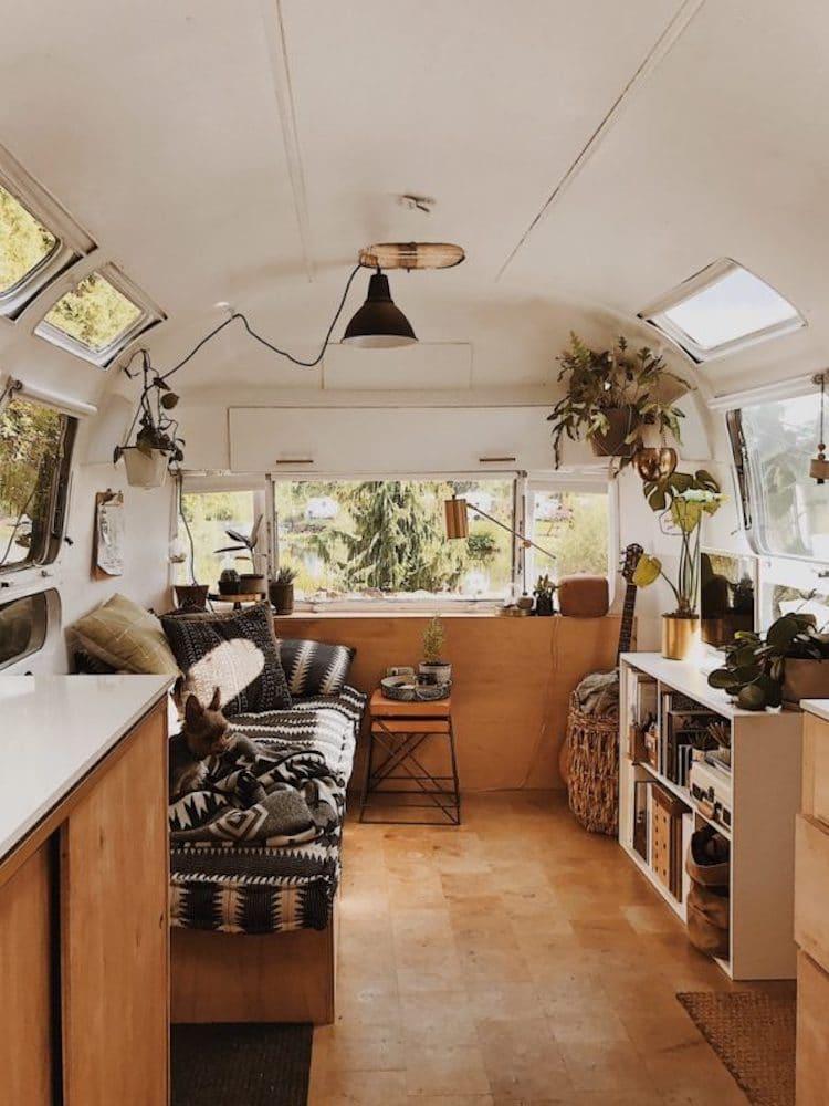 Imagem do interior de uma van, com madeira, plantas e pequenos móveis