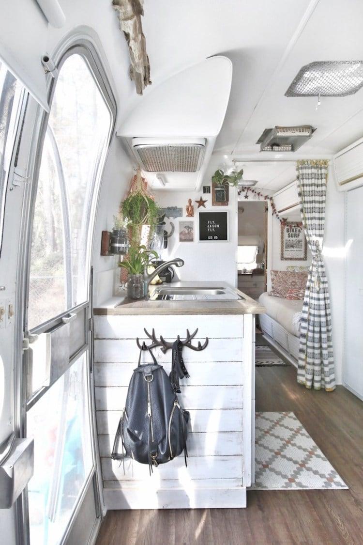 Imagem do interior de uma van e ao fundo um espaço para dormir, com cama de solteiro acoplada