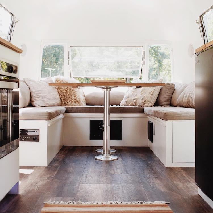 Imagem de um espaço com mesa e sofa dentro da van