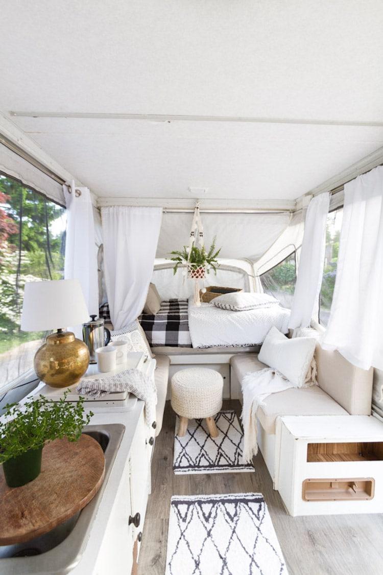 Imagem do interior de uma van, decorado com cortinas brancas, decoração clean, pequenos tapetes e objetos decorativos