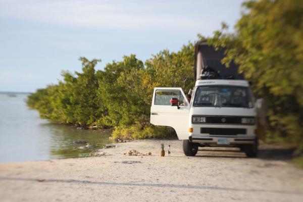 Imagem de van sobre um banco de areia, perto de vegetação e de um lago