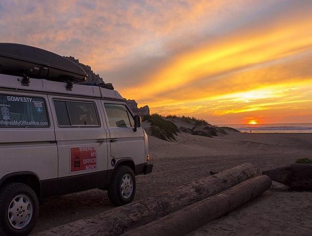 Imagem de van em uma praia, ao entardecer com o sol se pondo