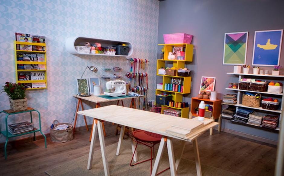 Imagem de ateliê feito em casa, com mesas e prateleiras de madeira em diferentes tamanhos