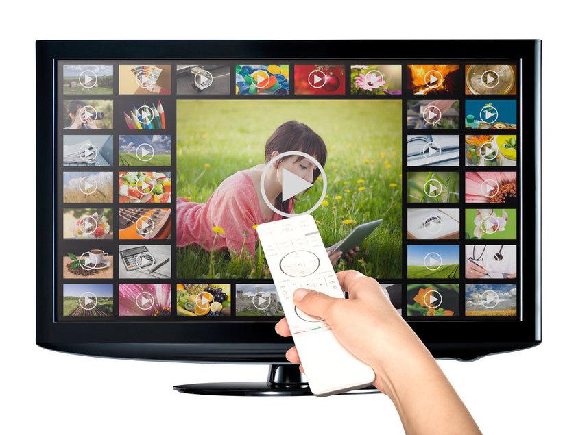 Imagem de controle remoto apontado para monitor em que várias possibilidades de filmes aparecem na tela