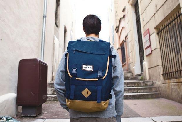 Imagem de modelo de costas, com uma mochila azul e mais descolada e informal