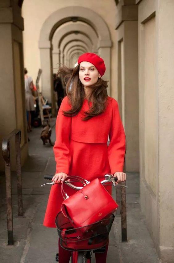 Imagem de modelo vestida toda de vermelho, com casaco comprido e boina, andando de bicicleta