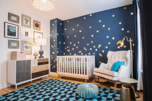 Imagem de quarto de bebê com decoração em tons azuis e brancos na parede, com decoração mais moderna