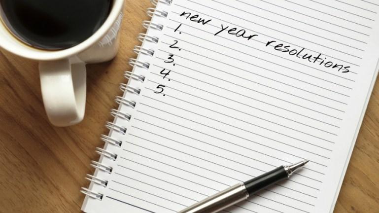 Imagem de uma lista a ser feita em caderno, com caneta e caneca de café ao lado, sobre a mesa
