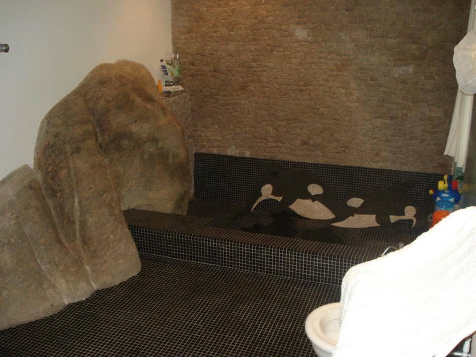 Imagem da parte interna da casa, com as pedras no revestimento interno e a banheira