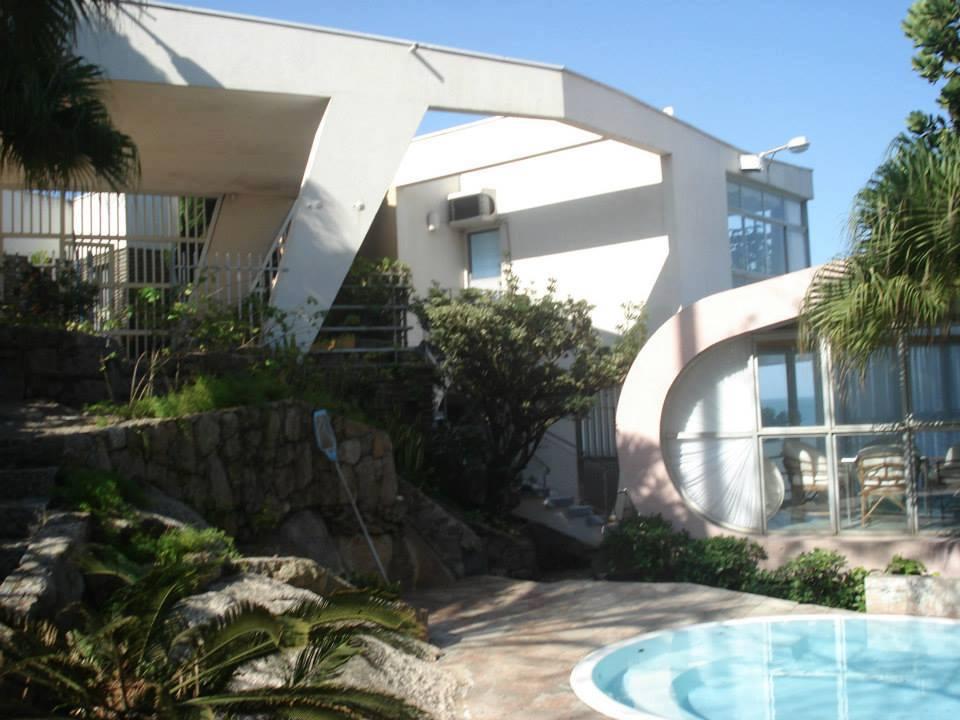 Imagem da parte interna da casa, com a piscina e o jardim