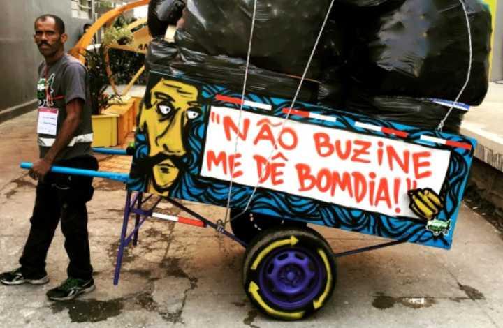 """Imagem de catador, e em sua carroça está escrito a frase """"não buzine, me dê bom dia""""."""
