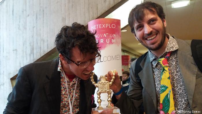 Imagem de Breno Castro Alves, coordenador do projeto, e Mundano, idealizador do aplicativo segurando o troféu