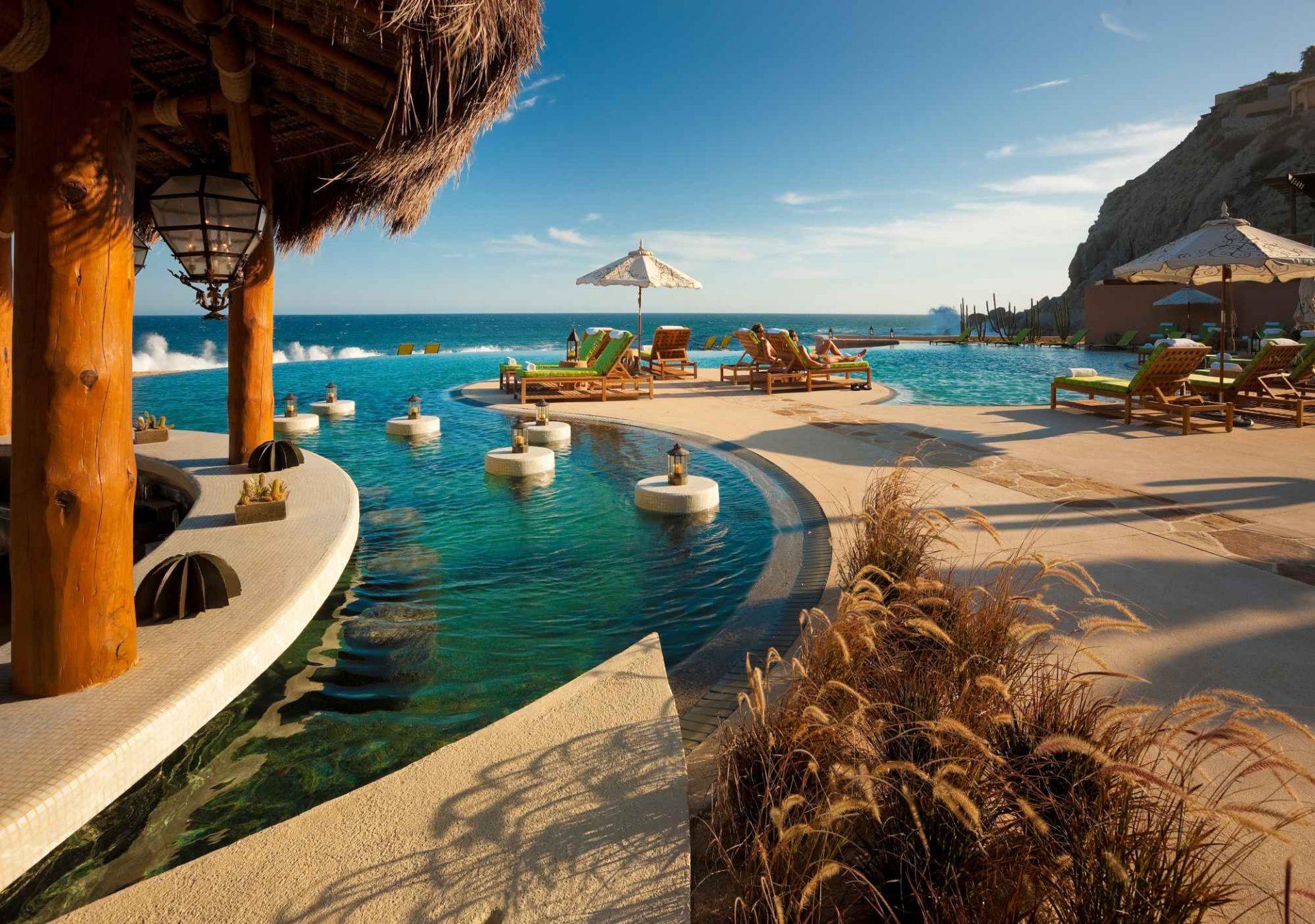Imagem da piscina e mar no horizonte do resort