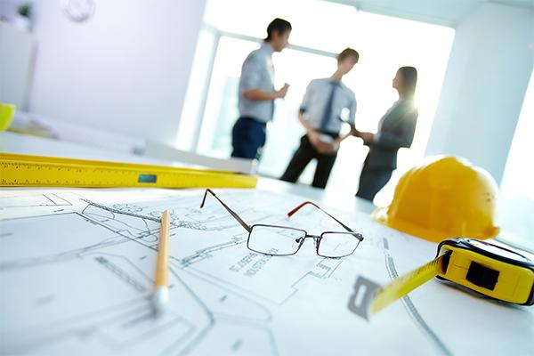 Imagem de materiais de arquitetos, como capacete, trema. Ao fundo três profissionais conversando