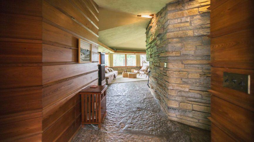 PlansMatter - Imagem interna com parede de pedra e madeira, na Kinney House