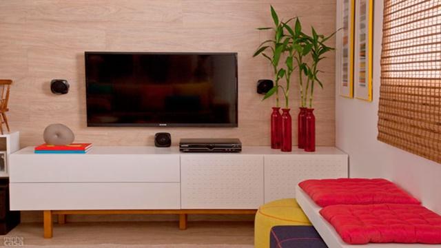 Imagem de rack branco, e televisão apoiada na parede, com decoração diversificada