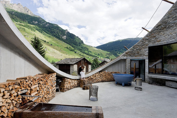 PlansMatter - Imagem de construção na Suíça, com design mais rústico, e de fundo montanhas na paisagem suíça